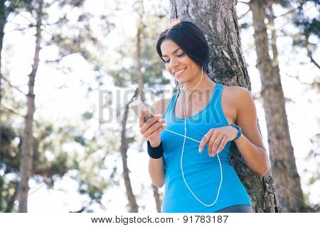 Smiling sporty woman using smartphone with headphones outdoors in park