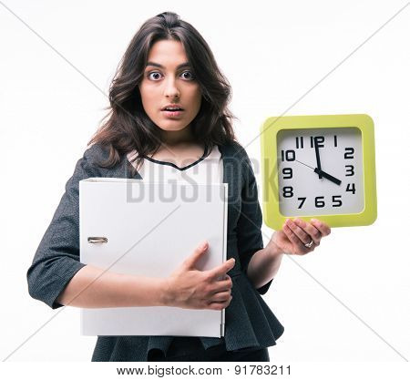 Surprised businesswoman holding folder and clock isolated on a white background. Looking at camera