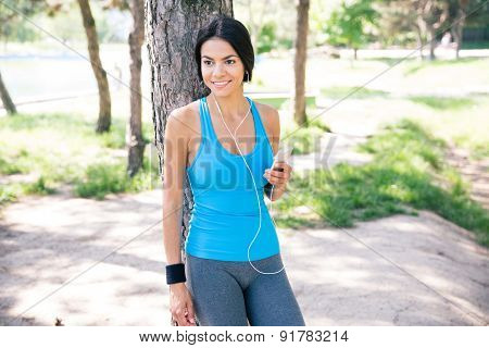 Happy thoughtful sporty woman standing with smartphone outdoors in park. Looking away