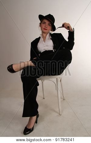 beautiful fashionable young woman in a black suit with a pipe