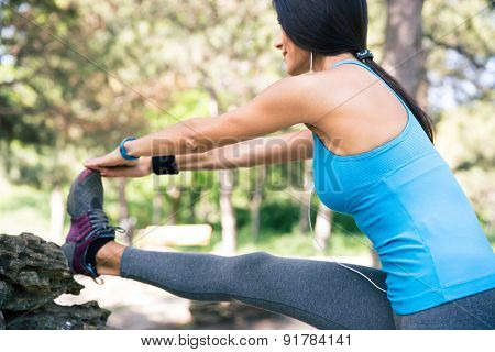 Fitness woman with headphones stretching legs outdoors in park