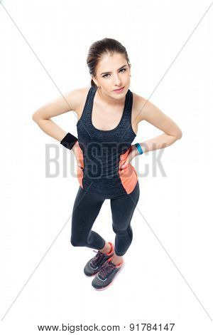 Cute fitness woman standing over white background and looking at camera