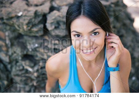 Portrait of a sporty woman with headphones outdoors. Looking at camera