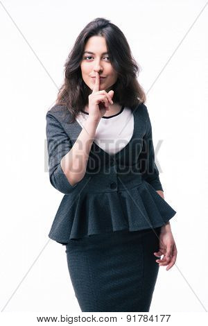 Businesswoman showing finger over lips isolated on a white background. Be quiet!!! Looking at camera