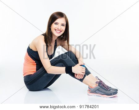Smiling fitness young woman sitting on the floor isolated on a white background. Looking at camera