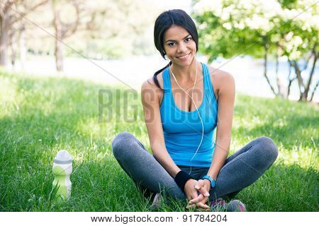 Happy cute sporty woman resting outdoors in park. Sitting on the green grass. Looking at camera