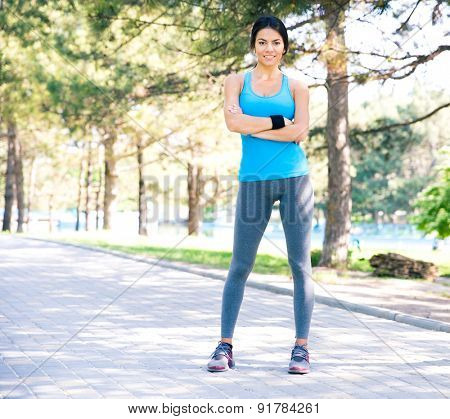 Full length portrait of a fitness pretty woman standing with arms folded outdoors in park and looking at camera