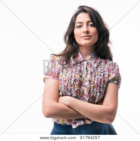 Cute serious woman standing with arms folded isolated on a white background. Looking at camera