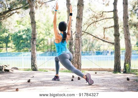 Back view portrait of a sporty woman stretching outdoors in park