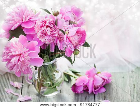 Pink roses in vase on wooden floor and bokeh background - retro styled photo
