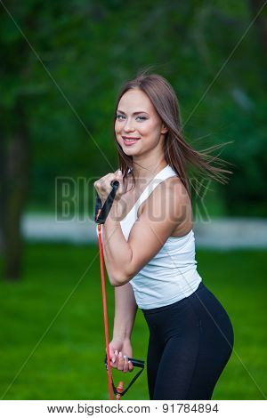 fitness, sport, people and lifestyle concept - smiling woman doing exercises with expander in outdoo