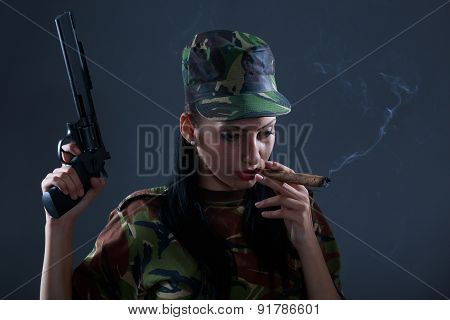 Female soldier in camouflage uniform with gun and cigar smoke