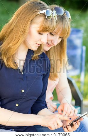 Pretty Young Women Using Smartphone In Summer Park