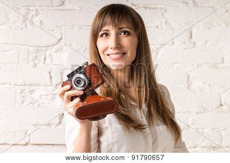 Pretty Smiling Woman With Old Film Camera On White Brick Wall