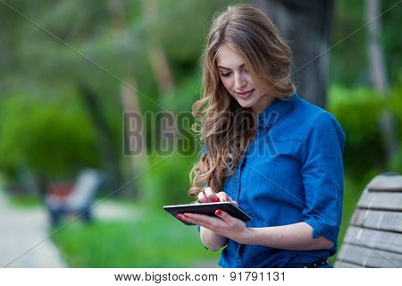 Side view of a young woman using  tablet computer on  park bench