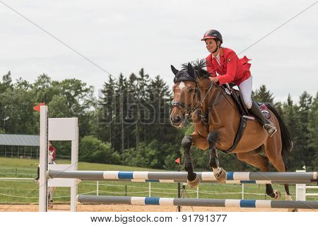 Closeup Side View Of  Horsewoman In Red Jacket Jumping
