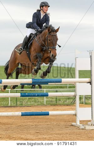 Horsewoman In High Jump Over A Obstacle. Vertically.