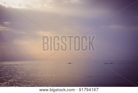 Three canoes sailing at sea during sunset
