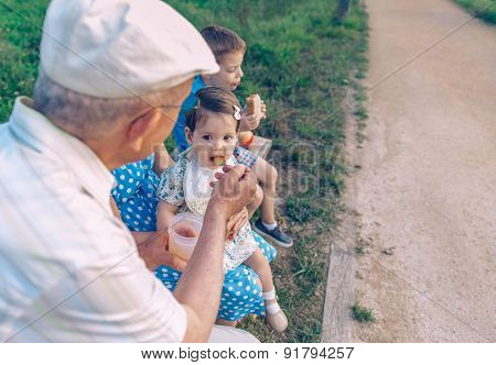 Senior man feeding to baby girl sitting in a bench