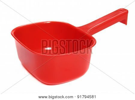 Plastic red ladle on a white background