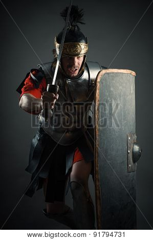 Roman legionary with sword and shield in the attack