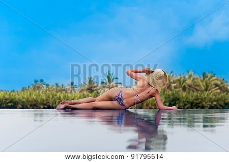 Woman With Hat Sunbathing On The Edge Of A Swimming  Pool
