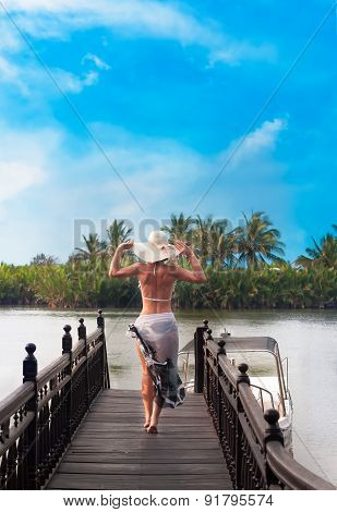 Woman  With Hat Seen  From Back Walking On River  Jetty