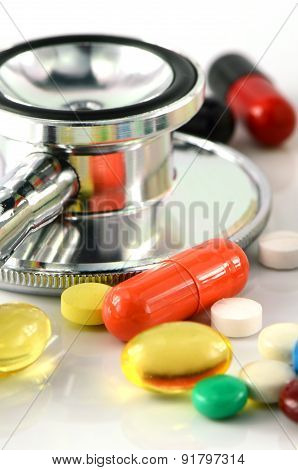 Stethoscope and Colorful of oral medications on White Background.