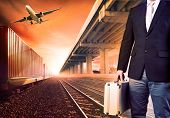 stock photo of railroad yard  - business man with metal breifcase investment standing against airpalne trains and ship port transport and logistic background - JPG
