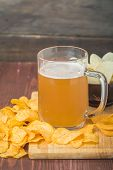 picture of potato chips  - Beer with foam in glass mug and potato chips in bowl on wooden table  - JPG
