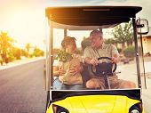 pic of grocery cart  - active elderly senior couple getting groceries on golf cart with orange lens flare and warm filter over image - JPG