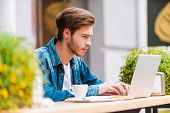 picture of concentration man  - Concentrated young man working on laptop while sitting at sidewalk cafe - JPG