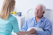 picture of visitation  - Carer visiting older sick man in hospital - JPG