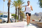 picture of palm  - Fit male runner running outside on boardwalk - JPG