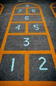 foto of hopscotch  - Children hopscotch game with orange borders and big light blue digits on concrete floor closeup - JPG