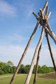 pic of tipi  - Tepee frame bound with rope in field with path and mound - JPG