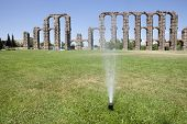 foto of aqueduct  - Grass Sprinklers wtih Roman Aqueduct of Merida at the bottom. Extremadura Spain