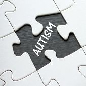 foto of autism  - The word Autism revealed by a missing piece of a jigsaw puzzle laid out on a blackboard surface - JPG