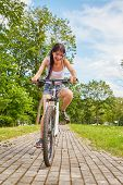 stock photo of cobblestone  - happy girl driving on bicycle on cobblestone in park