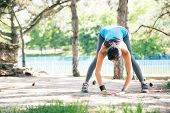 picture of stretching exercises  - Sporty woman doing stretching exercise outdoors in park - JPG