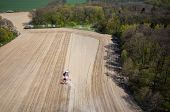 picture of cultivator-harrow  - Aerial view of the the tractor harrowing the large brown field in spring season - JPG