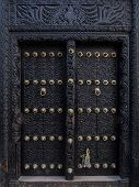picture of carving  - Vertical photo of old traditional black wooden carved door in Stone Town - JPG