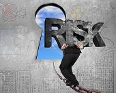 image of keyhole  - Man carrying big 3D RISK concrete word walking on old iron chain toward keyhole door with sky clouds view and gray concrete wall background - JPG