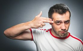picture of gunshot  - Funny man gesturing or taching his head at suicide concept over dark gray background - JPG