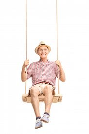image of swing  - Vertical shot of a playful senior swinging on a swing and looking at the camera isolated on white background - JPG