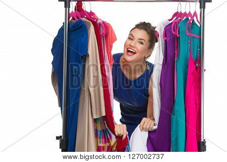 Beautiful happy young woman lookinh through hanger with many dresses. Isolated over white background. Copy space.