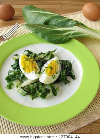 Eggs with fresh green chard vegetables on plate