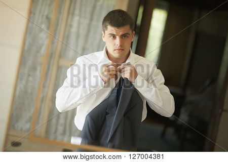 Handsome and strong man putting on official suit. Nice and slender groom wearing wedding suit and putting on cuffs in bedroom looking in mirror.