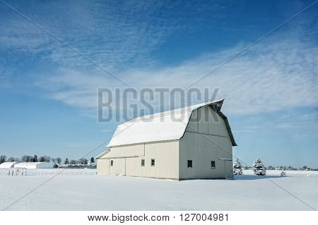 A rustic white Ohio barn covered in fresh snow with a bright blue sky background.