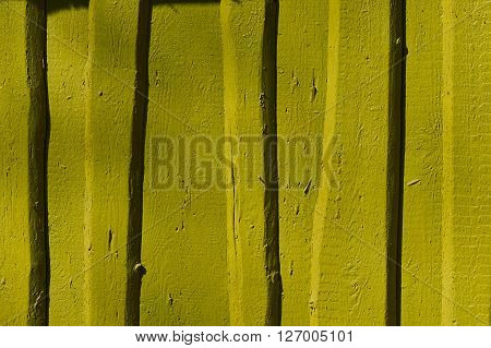 mustard flaky paint on a wooden fence.